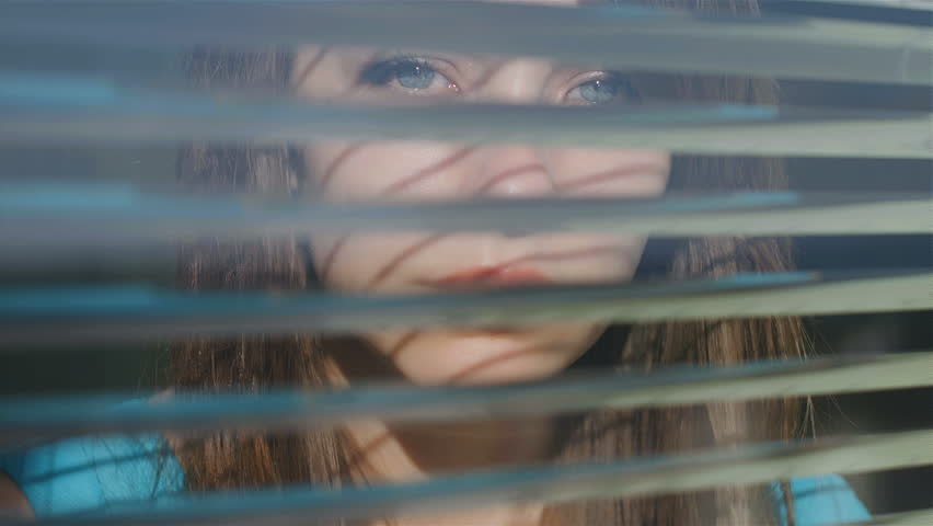 Beautiful young woman looking out the window through the blinds