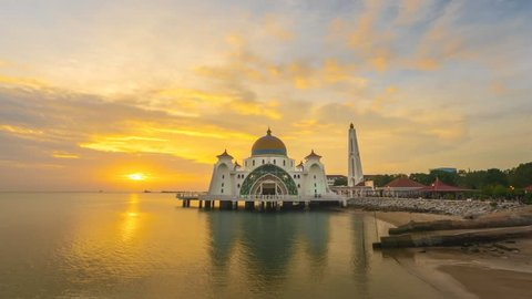 Dramatic Time lapse of sunrise and scattered clouds at Masjid Selat Melaka in Melaka, Malaysia. 4K resolution, 3840 x 2160. Night to day.