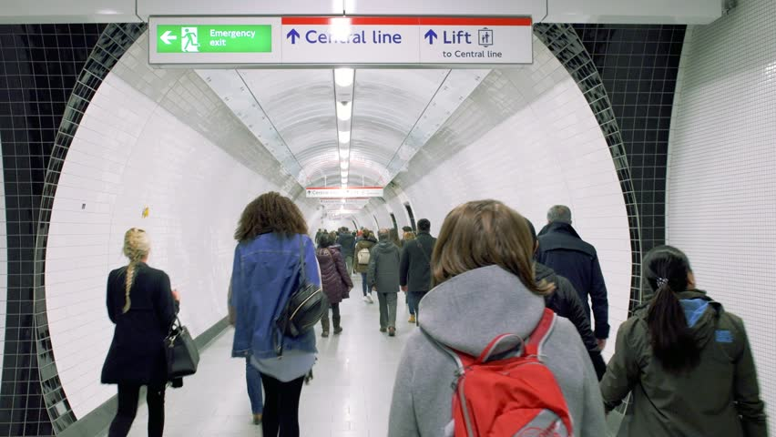 London, United Kingdom - Circa 2018: London underground metro tube with commuters walking to get the train to Central Line with security signs to Emergency Exit and lift - travel in British capital