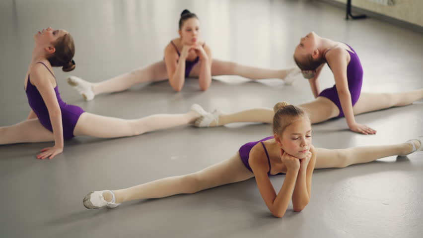 Flexible children ballet dancers doing stretching exercises on studio floor practising leg-split, backward and forward bends and arms movement.