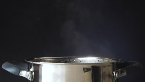 The cook salt the soup. The pan is on the stove. Steam comes from the pan. 4k