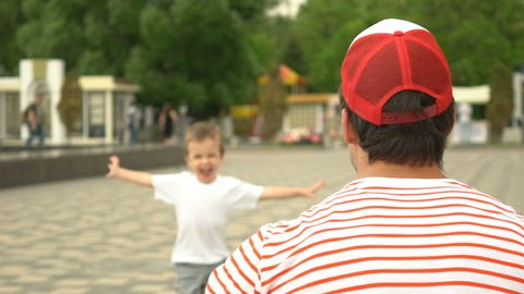 Son rushes into father's arms at park. Slowmotion footage