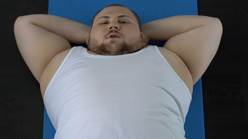 Stunt man doing sit-up exercise and resting on floor, lack of physical activity | Shutterstock HD Video #1011221228