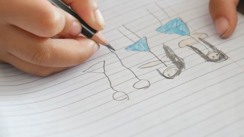 Hand close up of children drawing cartoons on paper