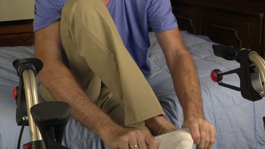 Senior man sits on edge of bed in front of walker, pulls on white socks. 4K UHD 3840x2160 Elderly staying independent  concept  | Shutterstock HD Video #1011252878