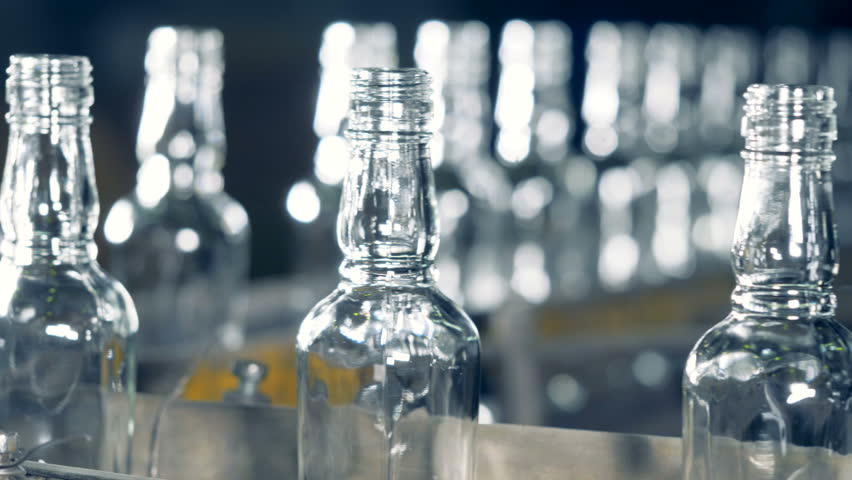 Ribbed necks of glass bottlings moving along the transporter in a close up | Shutterstock HD Video #1011263198
