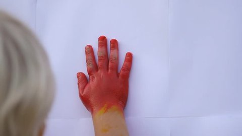Close up of cute child's hands making color handprints on the white  wall with lovely mother in slow motion 50fps