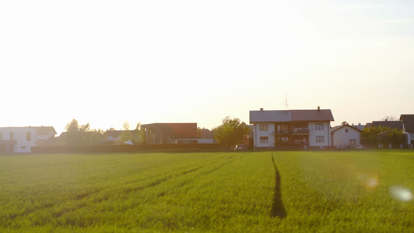 Car side window view of countryside homes with advertise sign in front 4K. Wide shot person view from car driving along a field and houses in background. A big blurred sign in front. | Shutterstock HD Video #1011274778