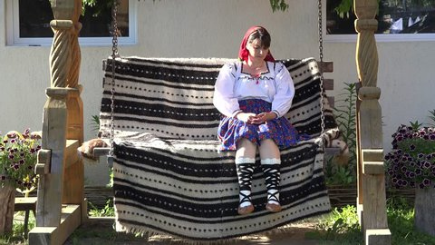 Attractive single woman wearing traditional costume sit on wooden swing, waiting, relaxing