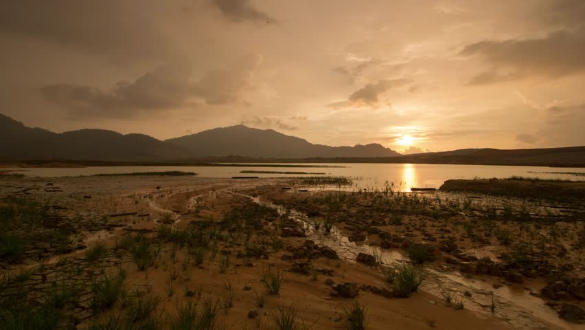 Timelapse golden cloud raining day at Mengkuang Dam. Beautiful wetlands with plant grow in the wetlands. | Shutterstock HD Video #1011285758