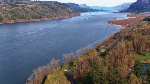 Drone aerial flyover of the towering rock at Rooster Rock State Park with the Columbia River Gorge in the background on a winter's day