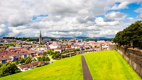 Derry, North Ireland. Aerial view of Derry Londonderry city center in Northern Ireland, UK. Sunny day with cloudy sky, city walls and historical buildings. Time-lapse, zoom in