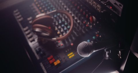 Close -up of microphone in music recording studio with sound mixer and equalizer control panel