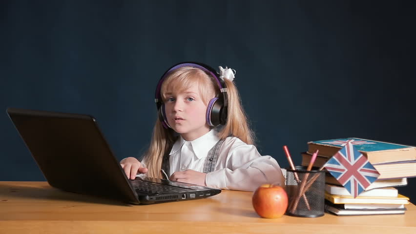 Focused schoolgirl using laptop in the classroom, doing the task on the computer at the desk with arranged books, concept of using technology at school and educational institutions | Shutterstock HD Video #1011309878