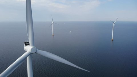 Offshore Windmill farm in the ocean  at the lake IJsselmeer by Urk Netherlands, isolated windmill park at sea, drone view from above out the sky bird eye view