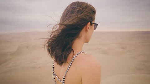 Portrait of Young Woman taking in landscape with hair blowing in wind looking at sunset at a desert oasis wearing white/black stripped fashionable tank shirt in Peru Slow Motion
