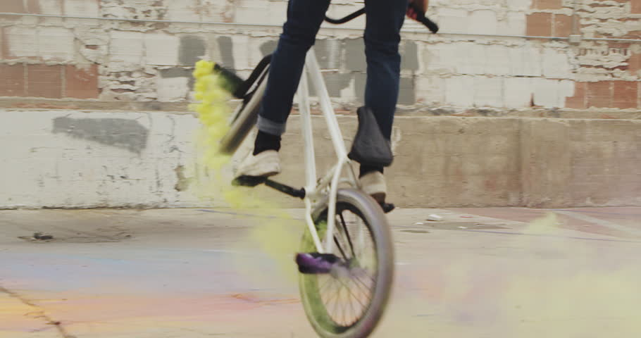 Close up of extreme BMX biker doing 360 spin  with purple and yellow colored smoke grenade trick in urban environment