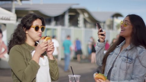 Excited Tourist Takes A Photo Of Her Friend Posing With Her Burger For Social Media (Shot On Red Scarlet-W Dragon In 4K, Slow Motion)