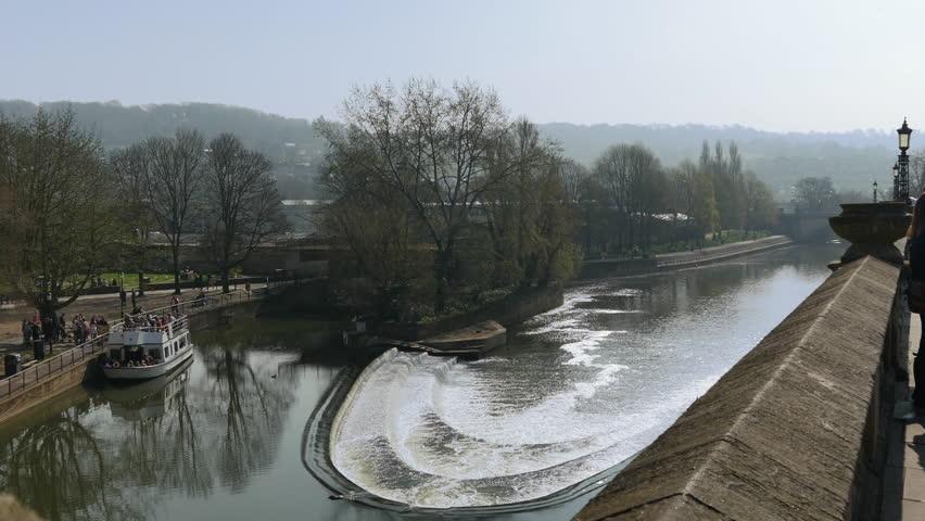 Pulteney Bridge weir, Bath, UK. River Avon flowing down the weir, daytime, sunny, bright exterior day. Historical landmark, tourist Vista.