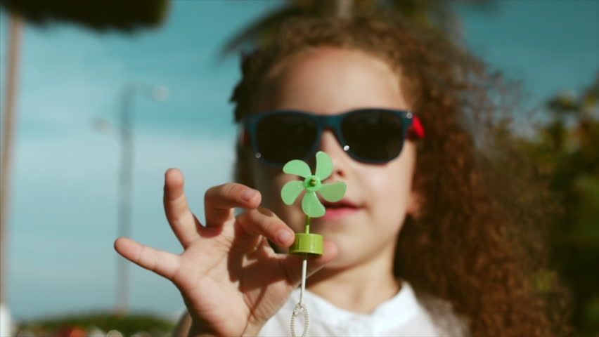 Close-up portrait of a happy cute little girl child with curly hair and red sunglasses looking into the camera at half covering her face with hand at