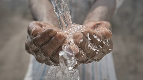 slow motion shot of splash of freshwater falling on poor man's hands against barren and dry farmland. Clean drinking water splashing on hands of the poor rural man in a drought affected area
