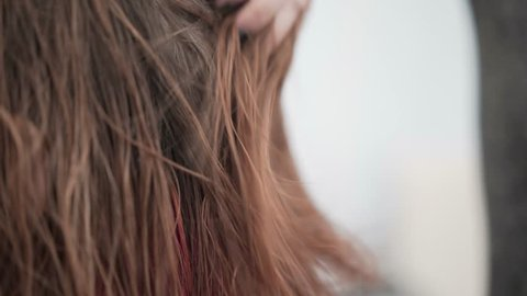 Side view of an unrecognizable young hairdresser drying her clients hair with a hairdryer and stroking it. Handheld real time close up shot
