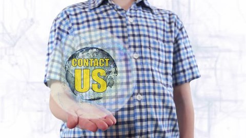 Young man shows a hologram of the planet Earth and text Contact us. Boy with future technology 3d projection on a modern white digital background