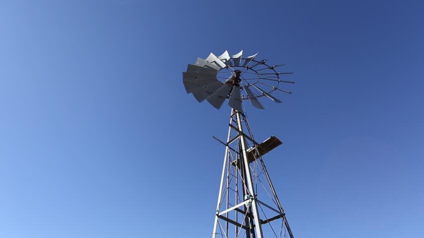 Hero shot looking up at a windmill windpump spinning against blue skies in Karoo South Africa