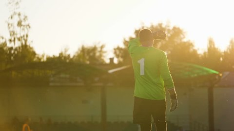 Tired goalkeeper wipes his forehead with his hand