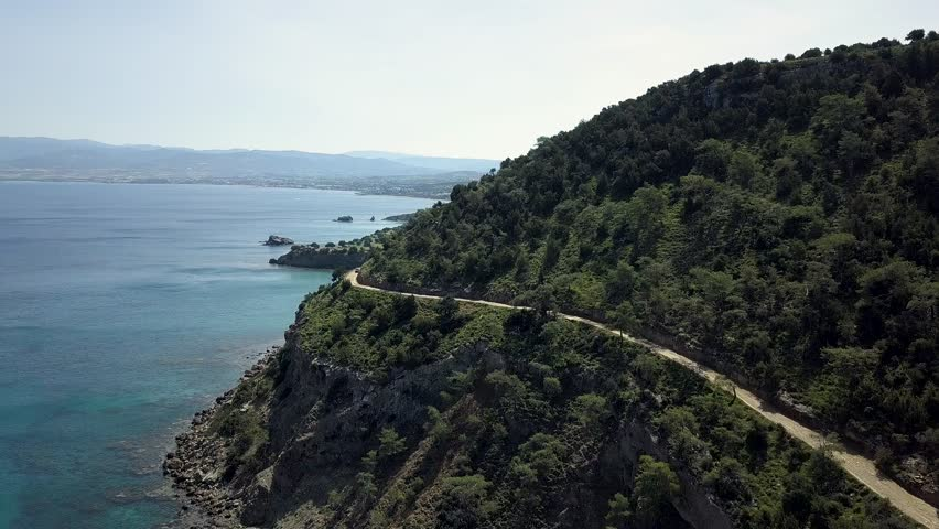 Meandering dirt road on a rocky cliff along the coastline of the sea along which the car drives. Surrounded by wild nature with rocks, bushes and forest in the hills. Shooting to the drone from above. | Shutterstock HD Video #1011437498
