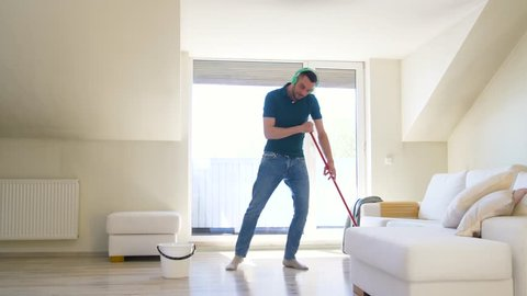 people, housework and housekeeping concept - happy man in headphones with mop cleaning floor and dancing at home