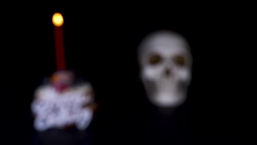 Cake and skull in a festive cap on a black background. 4k, dolly shot, defocusing, blur. | Shutterstock HD Video #1011463238