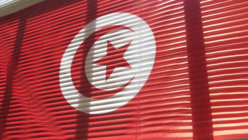 Tunisian flag hanging at wide jalousie window. Closeup  #1011468848
