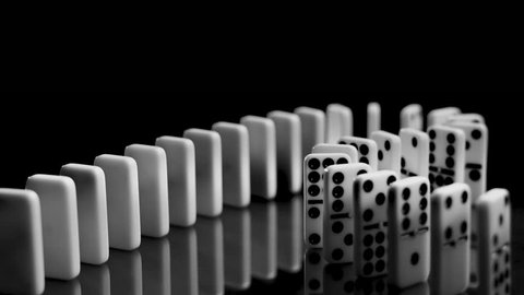 White dominoes standing in an s-curve. The stones are falling in slow motion from right to left.