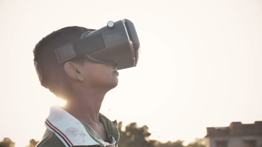 A young kid wearing VR glasses enjoying and looking around in amazement in an outdoor open field against the sun. An excited young boy wearing Virtual Reality glasses in rural India