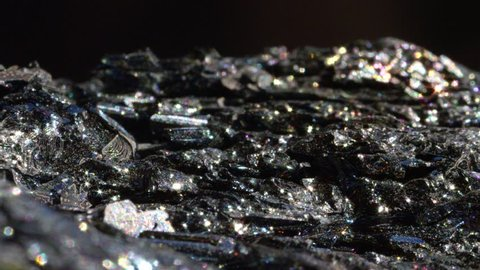 MACRO CLOSE UP: Black Hematite sparkling in variety of colors. Mineral known as blood stone after it's processed reveals its glowing and metallic sheen. Inexpensive iron oxide shimmering under light