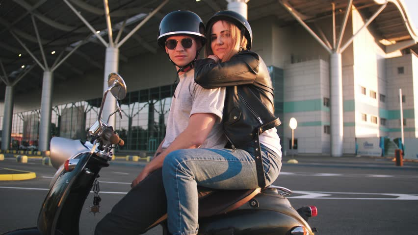 Happy young couple riding vintage scooter on urban background and having some fun, slow motion | Shutterstock HD Video #1011514238