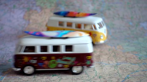 Model campervans with surfboards, on a map, with one passing the other. A travel/holiday/vacation concept.
