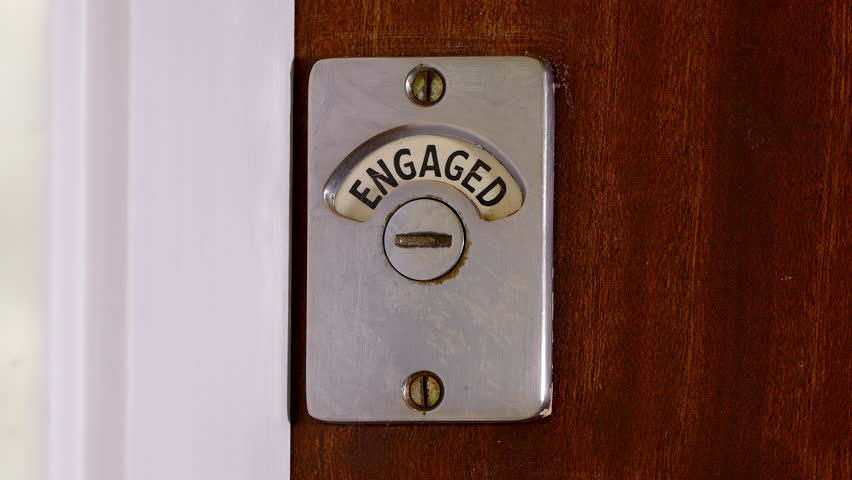 Closeup of someone exiting a public toilet / bathroom and closing the wooden door. The sign changes from engaged to vacant.