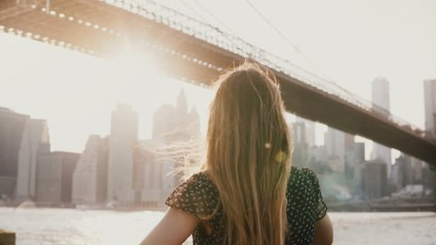 Back view of beautiful girl with hair blowing in the wind leaning against river embankment fence near Brooklyn Bridge 4K