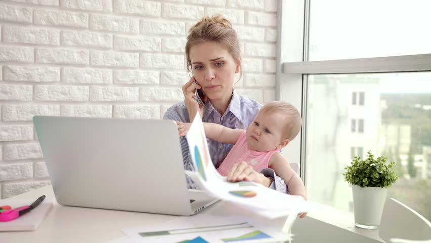 Baby distracted mother from conversation. Busy mom with child on hands speaking mobile phone. Working mother with baby at home. Modern woman working from home. Female employee with child girl