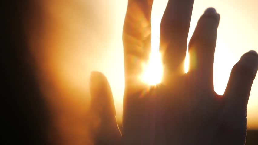 Girl looks at the sun through her hand #1011520658