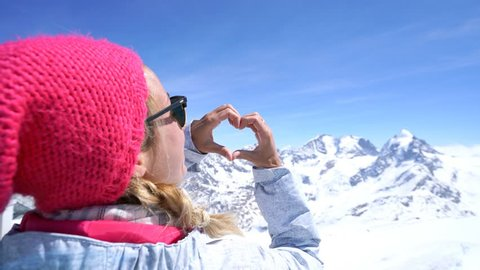 Young woman on ski slopes making heart shape on the stunning landscape. Woman on ski vacation in Switzerland, loving nature. 4K resolution