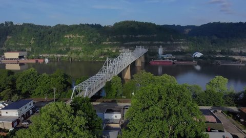 A slow, early morning aerial approach to the Ambridge Bridge spanning the Ohio River. Old factories and coal barges on the shoreline. Pittsburgh suburbs.