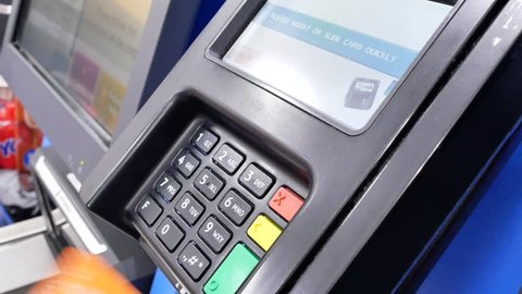 Coquitlam, BC, Canada - May 24, 2018 : Close up of woman paying foods by credit card at self-check out counter inside Walmart store with 4k resolution.
