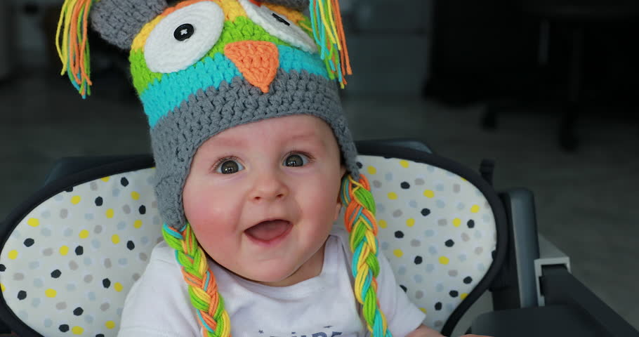 Beautiful Baby With A Funny Colored Wool Hat On The Head, Cute Six Month Old Baby Boy In High Chair. Close Up View - 4K Resolution