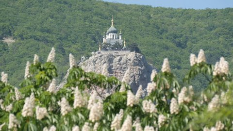 The Orthodox Church in Foros stands on a mountain, against a backdrop of flowering chestnuts