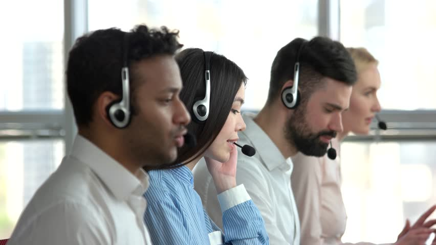 Young asian woman working and smiling. Smiling girl working in call center accompanied by her co-workers, side view. Asian woman helping to solve client's problems.