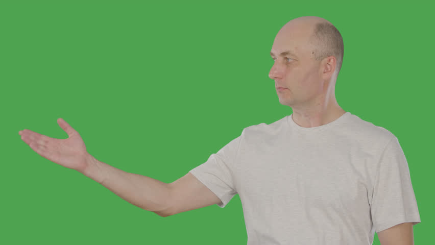 Serious mature man presenting something with hand on chroma key. Alphachannel, keyed green screen | Shutterstock HD Video #1011566108
