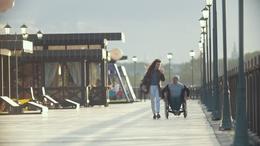 Disabled man in a wheelchair talking on the phone walking together her girlfriend on the quay #1011637508